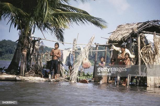 Eine sechsköpfige venezolanische Familie steht in dem Lagunendorf Sinamaica vor ihrem überschwemmten Haus Die aus Holz und Bastmatten bestehende...