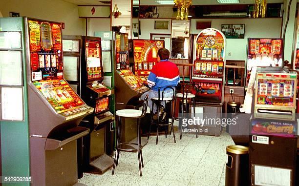 Eine Spielhalle in Jandia auf Fuerteventura mit diversen Spielautomaten Ein Mann sitzt auf einem langbeinigen Hocker und blickt auf die Anzeigefelder...