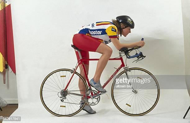 Eine Studioaufnahme einer Radrennsportlerin in voller Ausrüstung Sie nimmt die Wettkampfhaltung ein nach vorn gebeugt Unterarme auf den...