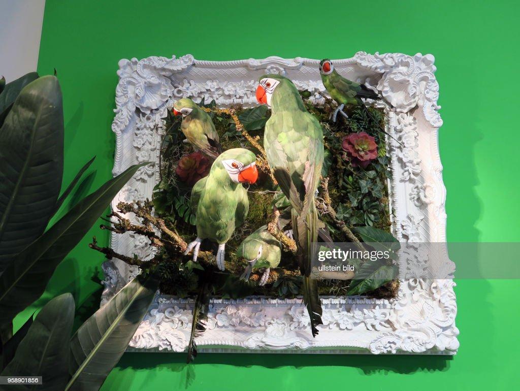 Eine Wanddekoration aus Pflanzen und künstlichen Papageien in einem ...
