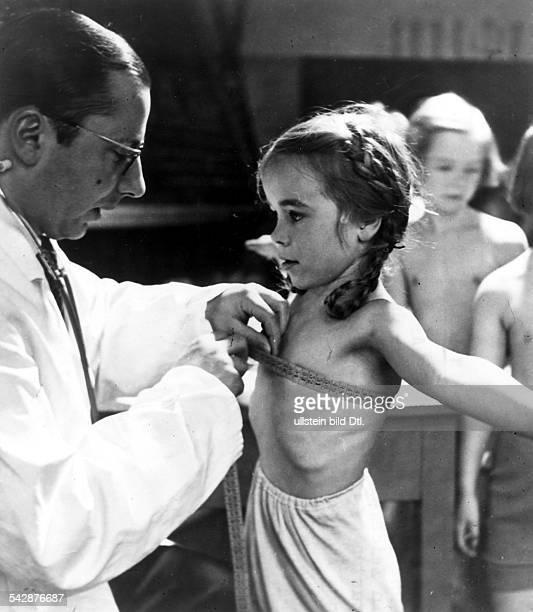 Einem Mädchen wird zur Einschulung voneinem Arzt der Brustumfang gemessen