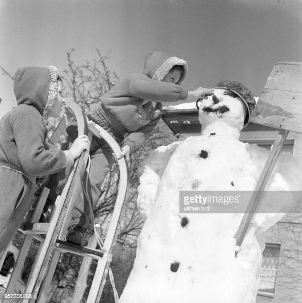 Einen Schlitten als Leiter wird von einem Kind genutzt um dem großen Schneemann die MöhrenNase ins Gesicht zu setzen Kinder bei Spielen imSchnee...
