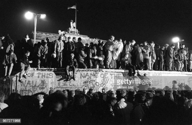 Einen Tag nach der Grenzöffnung in Berlin feiern tausende Menschen auf, vor und hinter der Berliner Mauer am Brandenburger Tor, aufgenommen am auf...