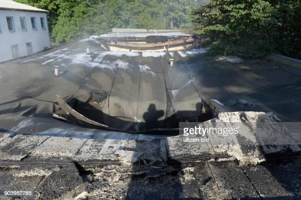 Eingestürztes Dach und durch Hitzeinwirkung verformte Dachhaut und Stahlträger während eines Brandes in einem einstöckigen Garagenkomplex in der...