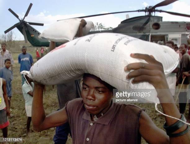 Einheimische laden am 632000 in der mosambikanischen Kleinstadt Machanga Reissäcke aus einem PumaTransporthubschrauber des Bundesgrenzschutzes Bei...