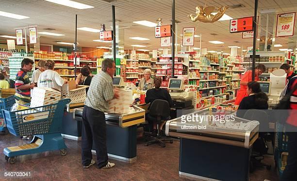 Einige Kunden packen im Kassenbereich eines spanischen Supermarktes in Jandia auf FuerteventuraSüd ihre Waren ein An einer Kasse steht ein blauer...