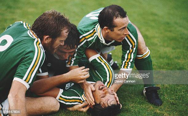 Eire goalscorer Mickey Walsh is congratulated after scoring the winning goal by from left Tony Grealish Michael Robinson and Liam Brady during a 1986...