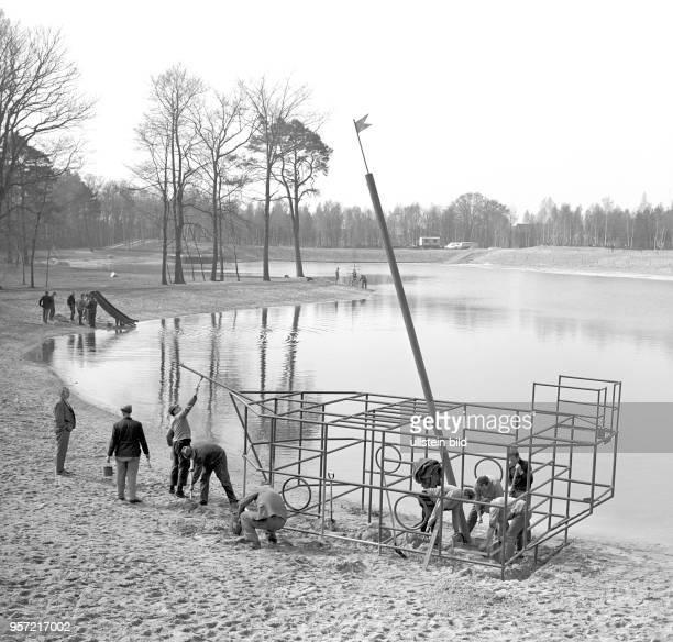 Eisenbahner vom Reichsbahnausbesserungswerk errichten für die Kinder am Strandufer des Madlower Badesees in Cottbus ein Klettergerüst in Form eines...