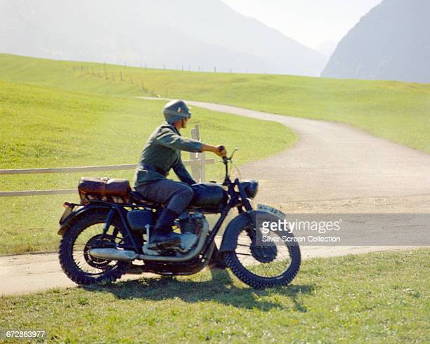 Either American actor Steve McQueen or his stuntman Bud Ekins wearing a German military uniform sitting astride a Triumph Bonneville motorcycle in...