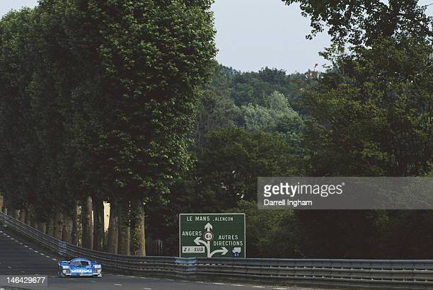 Eje Elgh of Sweden drives the Team Schuppan Omron Porsche 962C past the Le Mans road sigh along Tertre Rouge during the FIA World Sportscar...