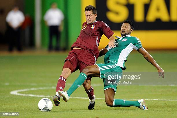Ejike Uzoenyi of the Nigeria Soccer Team and Cesar Gonzalez of the Venezuela National Soccer Team in action during an exhibition game at Marlins Park...