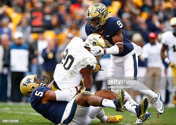Ejuan Price and Jordan Whitehead of the Pittsburgh Panthers tackle CJ Prosise of the Notre Dame Fighting Irish for a loss in the first quarter during...