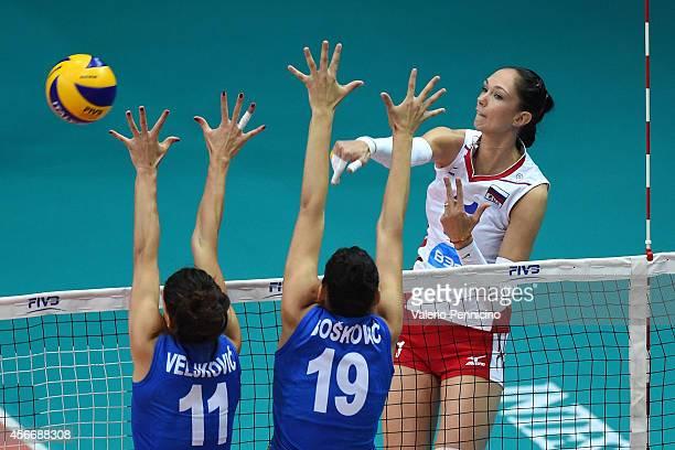 Ekaterina Gamova of Russia spikes as Tijana Boskovic and Stefana Veljkovic of Serbia block during the FIVB Women's World Championship pool F match...