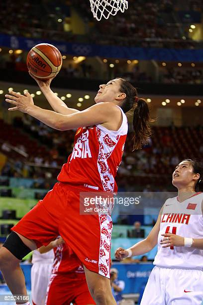 Ekaterina Lisina of Russia goes to the basket past Song Xiaoyun of China during the women's basketball bronze medal game at the Beijing Olympic...