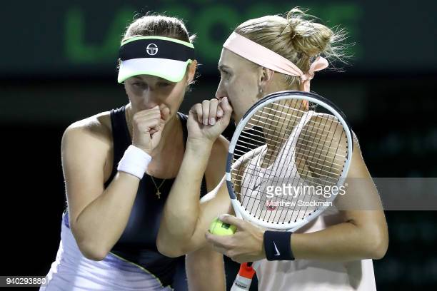 Ekaterina Makarova of Russia and Elena Vesnina of Russia confer between points while playing Coco Vandeweghe and Ashleigh Barty of Australia during...