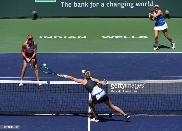 Ekaterina Makarova of Russia returns against Kristina Mladenovic of France and Timea Babos of Hungary during Day 11 of BNP Paribas Open on March 15...