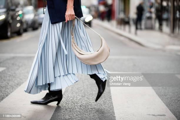 Ekaterina Mamaeva is seen wearing asymmetric blue pleated skirt Proenza Schouler black boots Khaite navy jacket Giuliva creme white bag The Row on...