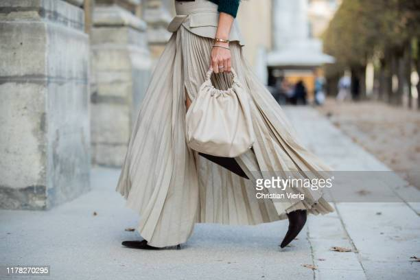 Ekaterina Mamaeva is seen wearing beige pleated skirt with slit AWAKE Mode sweater Saint Laurent boots and bag The Row belt Brunello Cucinelli during...