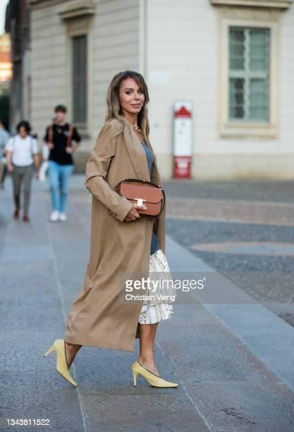 Ekaterina Mamaeva is seen wearing Dress JW Anderson, trench coat LA Collection, shoes Bottega Veneta, handbag Celine, necklace Laura Lombardi,...