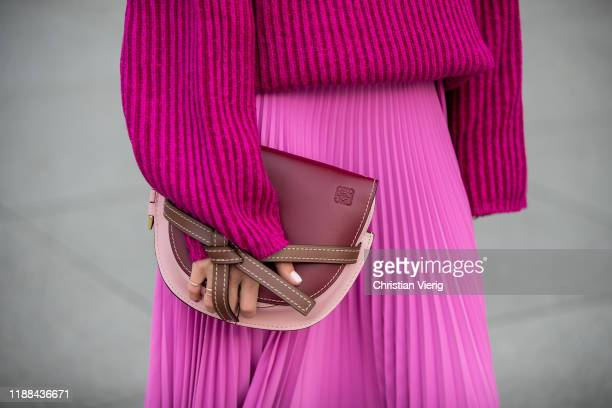 Ekaterina Mamaeva is seen wearing pink turtleneck knit sweater Acne Studios, pink pleated skirt AWAKE Mode, handbag Loewe on November 17, 2019 in...