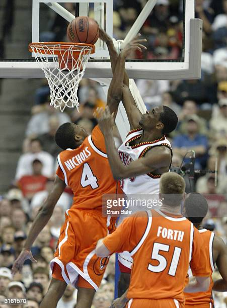 Ekene Ibekwe of the Maryland Terrapins dunks over Demetris Nichols of the Syracuse Orangemen in the second round game of the NCAA Division I Men's...