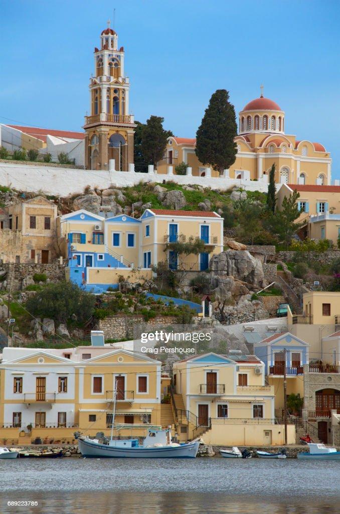 Ekklisia Evaggelistria (Annunciation Church) above pastel-coloured houses and Symi Harbour. : Stock Photo