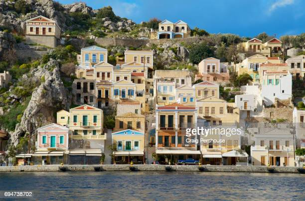ekklisia evaggelistria (annunciation church) above pastel-coloured houses and symi harbour. - symi stock photos and pictures