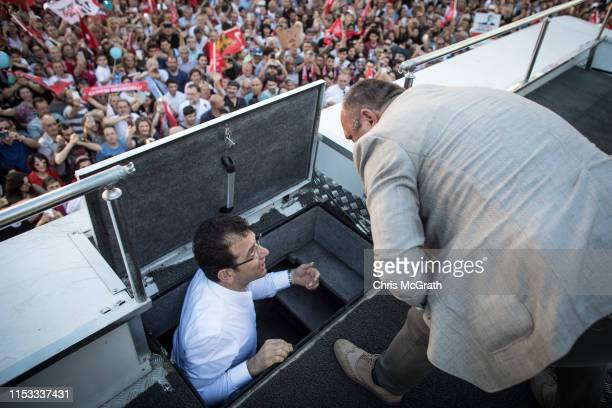 Ekrem Imamoglu CHP Party candidate for mayor of Istanbul speaks with his head of security before speaking to supporters on the roof of his campaign...