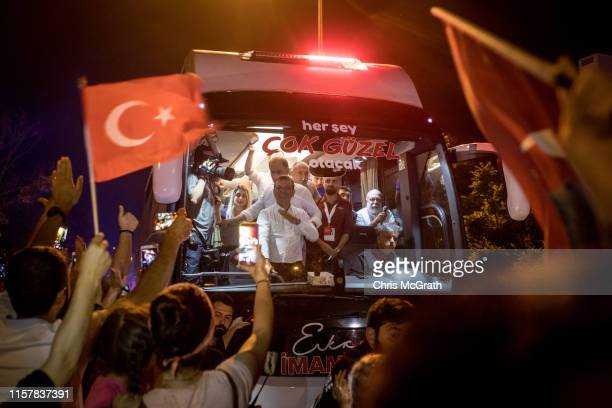 Ekrem Imamoglu of the Republican People's Party waves to supporters from his campaign bus as he arrives to his victory rally after AKP party...