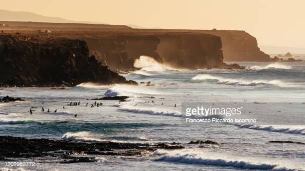 el cotillo cliffs and beaches with waves and surfers at sunset, fuerteventura - surf stock pictures, royalty-free photos & images