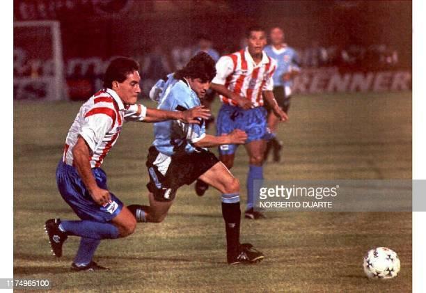 El delantero Uruguayo Marcelo Otero escapa de la marca del defensa paraguayo Carlos Gamarra en el partido que se disputa en Asuncion el 30 de abril...
