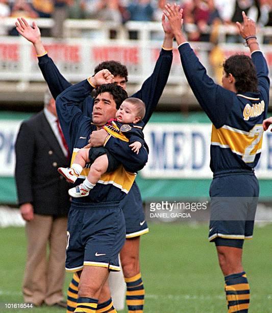 El futbolista Diego Maradona alzando en brazos a un sobrino no identificado saluda a los fans del Boca Juniors 21 septiembre en Buenos Aires al...