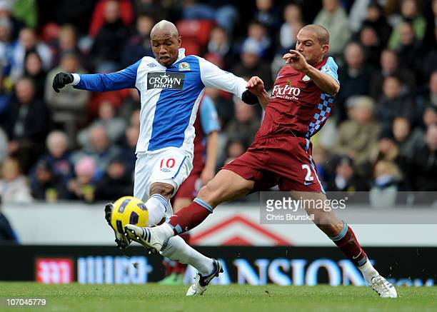 El Hadji Diouf of Blackburn Rovers is challenged by Luke Young of Aston Villa during the Barclays Premier League match between Blackburn Rovers and...