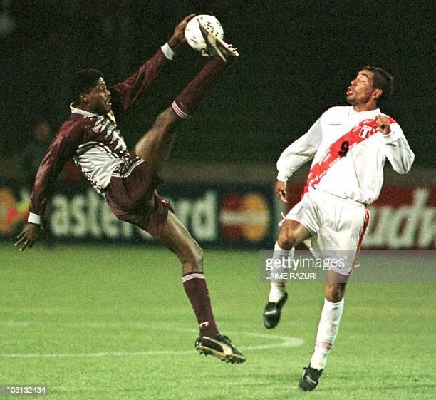 El jugador seleccion nacional de futbol de Venezuela Alexander Echenique salta con el balon frente a su similar peruano Paul Cominges durante el...
