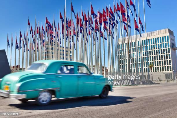 el malecón de la habana cuba abandonada embajada de estados unidos en segundo plano - bandera cubana fotografías e imágenes de stock