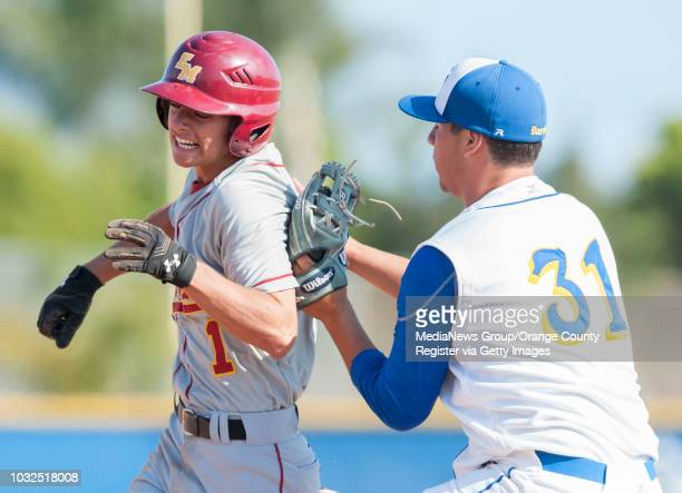 El Modena pinch runner Paul Gomez is tagged out by Fountain Valley pitcher Travis Burleson after being fooled by a fake pickoff attempt during the...