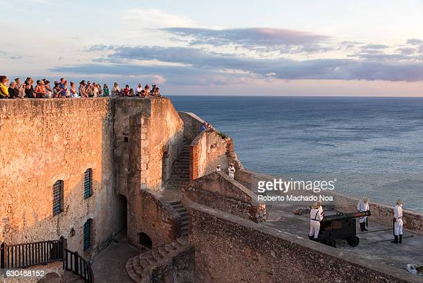 El Morro or Saint Peter of the Rock Castle Tourists look down from wall to see men loading an ancient cannon The landmark is a Unesco World Heritage...