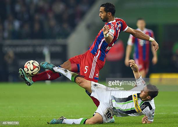 El Mouttaqi Benatia of Muenchen is challenged by Max Kruse of Moenchengladbach during the Bundesliga match between Borussia Moenchengladbach and FC...