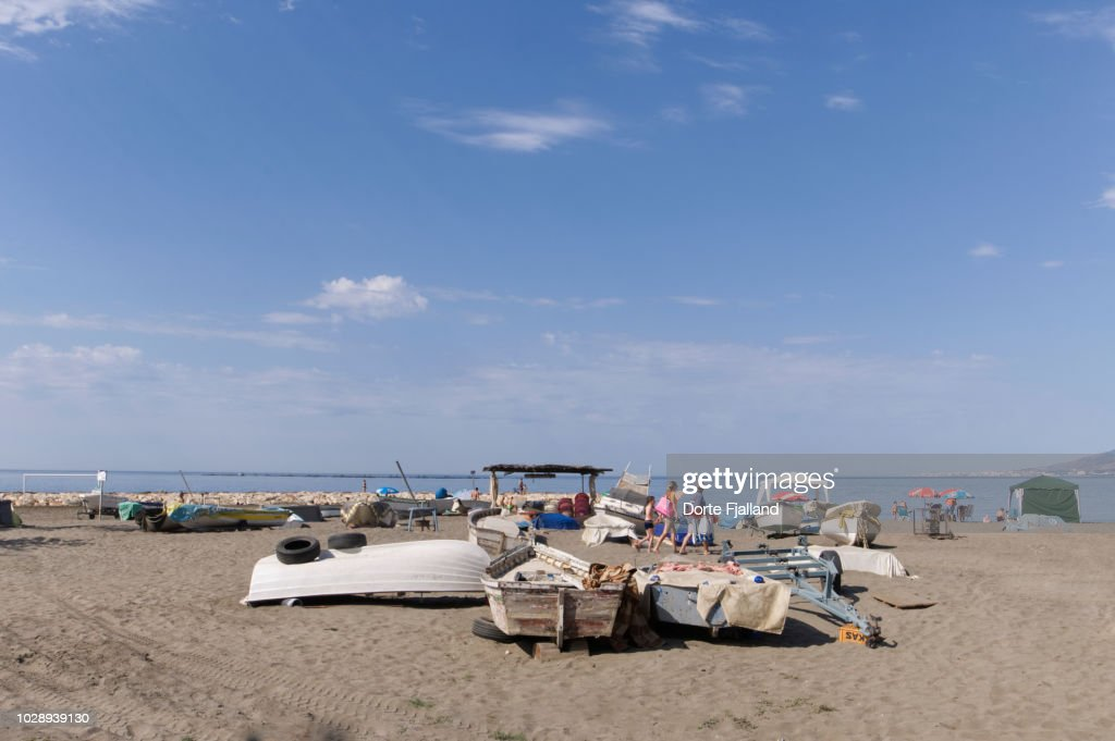 El Palo beach early Summer morning with blue sky, some people and small boats in the sand : Foto de stock