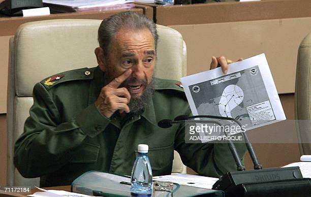 El presidente cubano Fidel Castro muestra un mapa meteorologico con la descripcion de una depresion tropical cuyas lluvias azotan la isla de Cuba el...