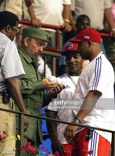 El presidente cubano Fidel Castro recibe en La Habana el 21 de marzo de 2006 de manos de Eduardo Paret capitan del equipo cubano de beisbol dos...
