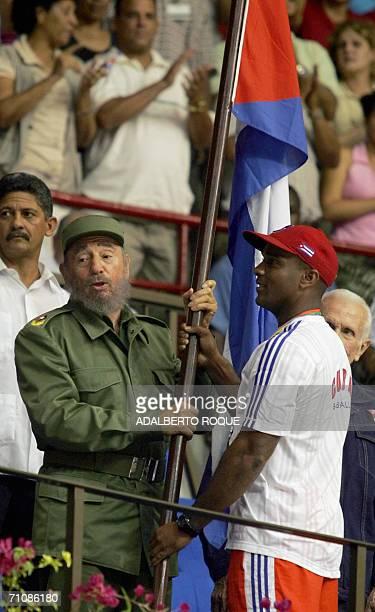 El presidente cubano Fidel Castro recibe en La Habana el 21 de marzo de 2006 de manos de Eduardo Paret capitan del equipo cubano de beisbol la...