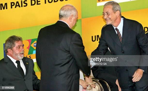 El presidente de Brasil Luiz Inacio Lula da Silva observa al vice presidente y nuevo ministro de Defensa Jose Alencar y al ministro saliente Jose...