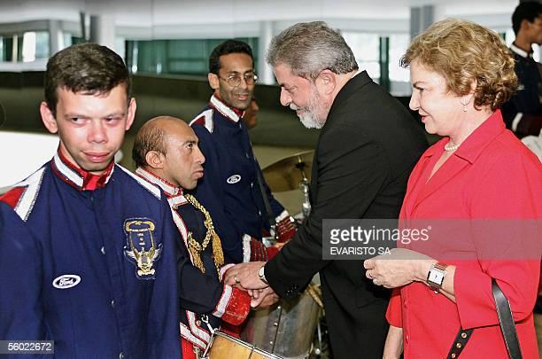 El Presidente de Brasil Luiz Inacio Lula da Silva y su esposa Marisa Leticia saludan a los miembros de un conjunto musical integrado por personas con...