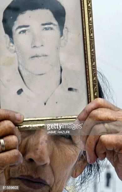 El retrato de Gilmer Leon desaparecido en 1992 es mostrado por su madre Hermelinda Velasquez durante una protesta masiva el 25 de octubre de 2004 en...