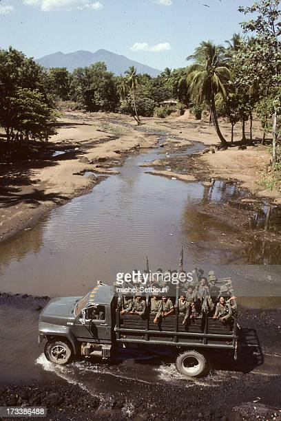 CONTENT] El Salvador civil war army truck with soldiers pass a river because the road is destroyed near Ussulutan