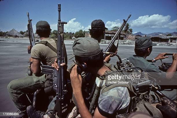 CONTENT] El Salvador civil war soldiers patrol in El Cuco Beach occupied by the army