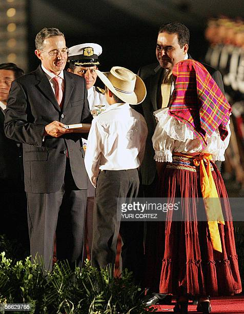 Colombian President Alvaro Uribe recives a tipical gift from two child wearing traditional clothes during a welcoming ceremony by salvadorean...