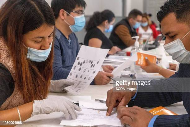 El Salvadoran Pop-up Consulate volunteer helps an El Salvadoran to fill a form for a new passport. The El Salvadoran Consulate is responsible for...
