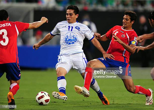 El Salvador's Rodolfo Zelaya dribbles the ball toward the goal as Costa Rica's Jhonny Acosta and Celso Borges apply defensive pressure during...